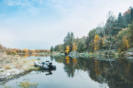 Fishing from an inflatable boat on an autumn river.