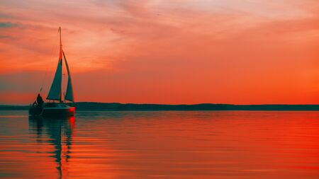 Sailing boat floats on the lake at sunset. Foto de archivo