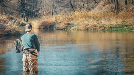 Fly fishing on a forest river background