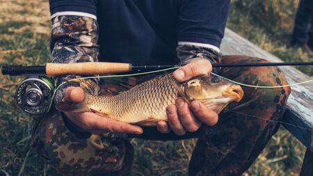 Fisherman holds a fish in his hand.