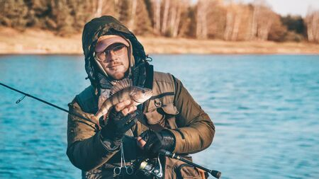 Fisherman holds a perch in his hand.