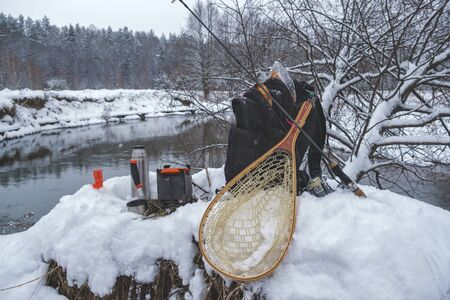 A picnic on a fishing trip, on a snow-covered winter river.