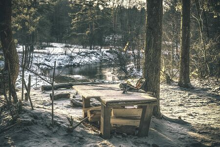 Fishing gear on the shore of a winter stream.