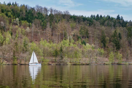 Sailing boat on a lake on the background of a spring forest.