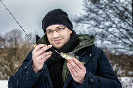 The man caught the first fish on ice fishing.