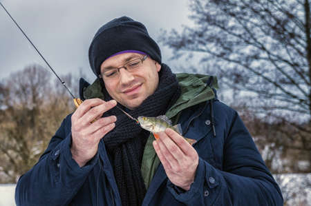 The man caught the first fish on ice fishing. Archivio Fotografico