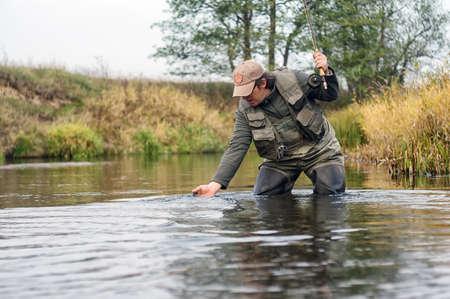 Happy fisherman pulls a fish.