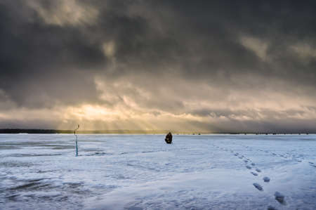 Fisherman on a background of storm clouds. Winter ice fishing on the lake.