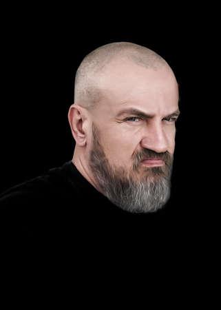 Brutal man on a black background. Emotion is discontent, anger.