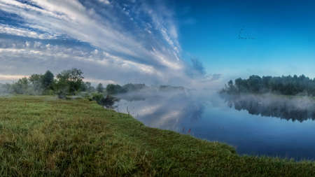 Evening on the river. Fog over the river on a background of blue sky and beautiful clouds.
