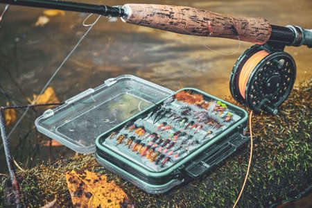 Fly rod and fly box on the bank of the stream.