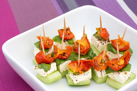 amuse: Plate of small feta, cucumber and tomato appetizers on toothpicks
