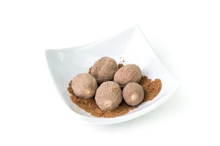 nutmeg: Bowl of nutmeg on a white background, studio isolated Stock Photo