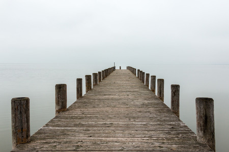 Deserted jetty, pier in foggy weather, horizontal shot