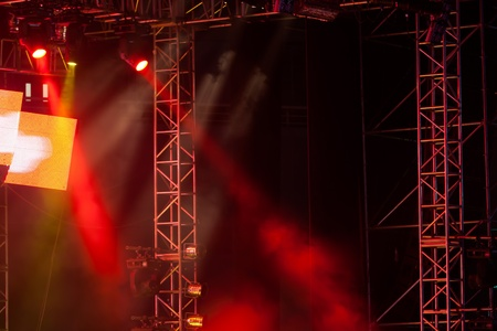 Image of red stage lights, thick fog creates drama