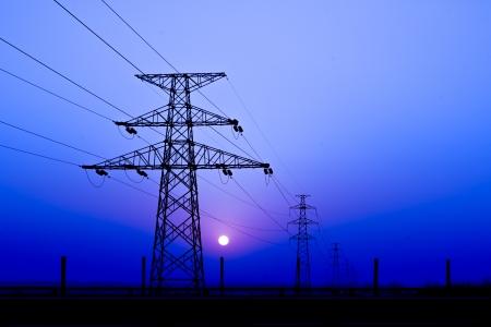 electricidad industrial: Puesta del sol bajo la torre de alta tensi�n en el fondo