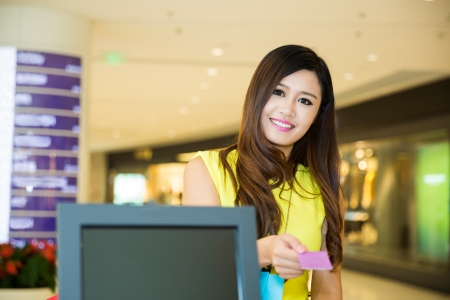 paying: woman doing shopping in mall and paying by credit card at the pay desk