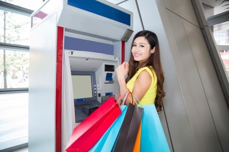 jonge vrouw die geld van creditcard bij ATM.
