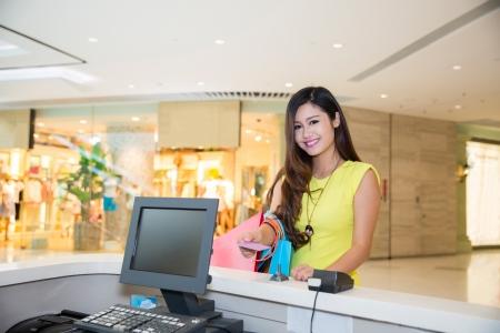 여성 쇼핑몰에서 쇼핑을하고 지불 책상에 신용 카드로 지불