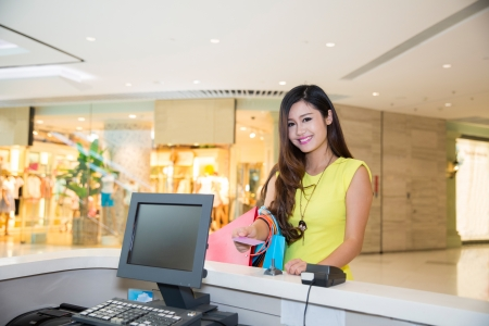 woman doing shopping in mall and paying by credit card at the pay desk