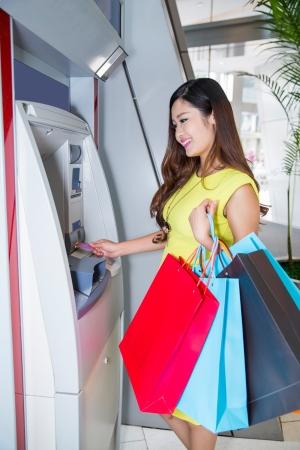 젊은 여자가 ATM에서 신용 카드에서 돈을 인출.
