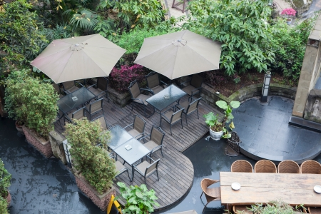 house patio with table and chairs under umbrella, there are a lot of vegetation around.