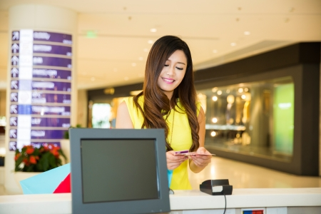 woman doing shopping in mall and paying by credit card at the pay desk photo