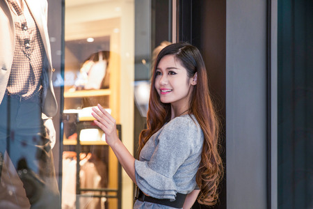 window shopper: young woman carrying shopping bags and smiling in mall Stock Photo