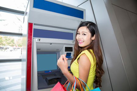 young woman withdrawing money from credit card at ATM