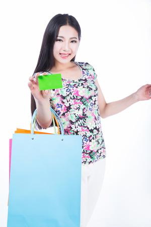 attractive girl with shopping bags and credit card on a white background photo