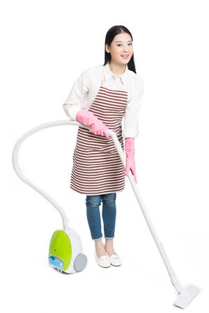 젊은 갈색 머리 여자 사용 진공 청소기, 흰색 배경.