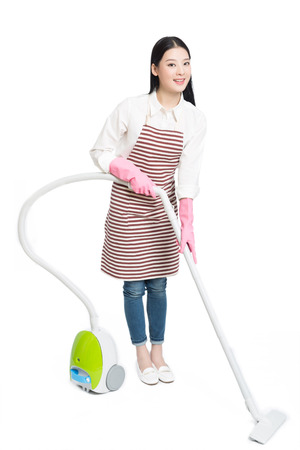 young brunette female uses vacuum cleaner, white background.
