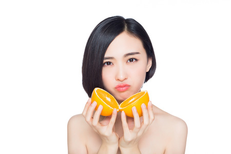 close up food: young woman with oranges in her hands, white background