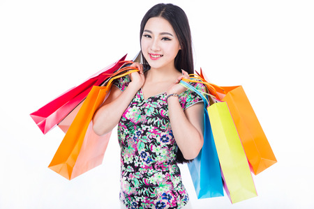 asian girl shopping: young brunette woman holding colorful shopping bags isolated on white background.