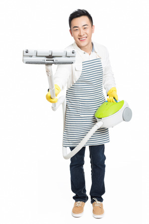 hoover: chinese young man with a vacuum cleaner, white background Stock Photo