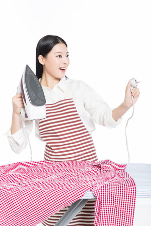Steam iron: young housewife ironing isolated on white background