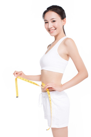 woman controlling her measures using a tape, white background Stockfoto