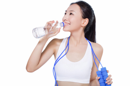 beautiful fitness woman with bottle of water and skipping rope. sport. white background.