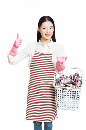 young woman holding a basket of folded laundry. white background.