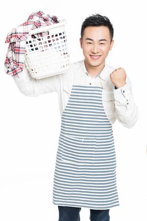 man laundry: cheerful man holding a laundry basket isolated on white background