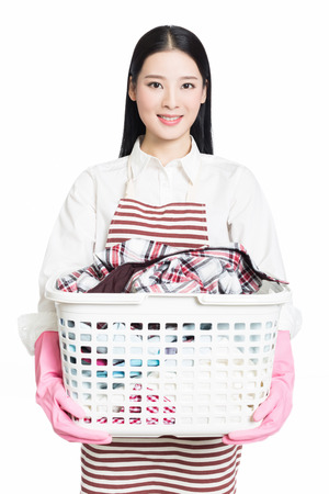 young woman holding a basket of folded laundry. white background. photo