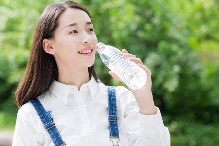 green water: girl drinking bottled water, asian woman