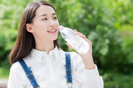 tomando agua: niña bebiendo agua embotellada, mujer asiática