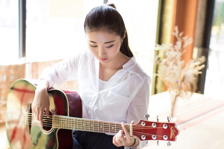 chinese adult: chinese black hair girl playing acoustic guitar