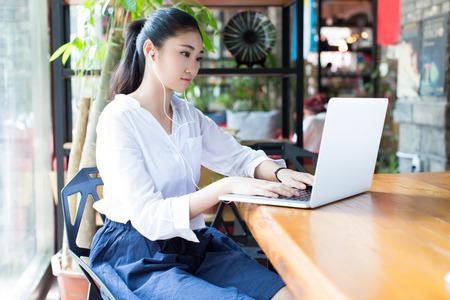 카페에서 음악을 노트북을 사용하고 듣고 중국 학생