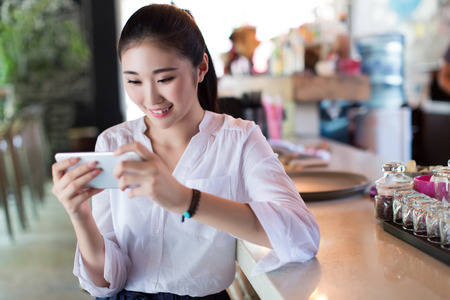 mobile internet: beautiful young woman using her mobile phone in bar Stock Photo