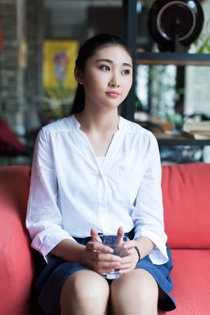 red sofa: Chinese girl sitting on a red sofa and holding a cup of water