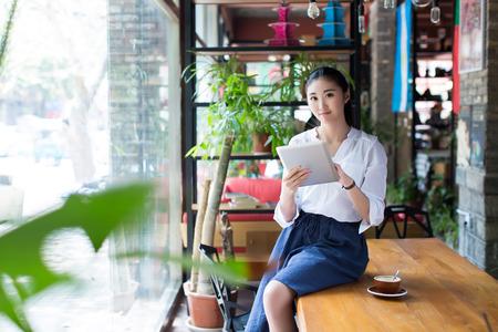 태블릿을 사용하는 카페에서 테이블에 앉아 젊은 여성