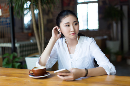 woman listening to music: beautiful woman using smartphone and listening to music
