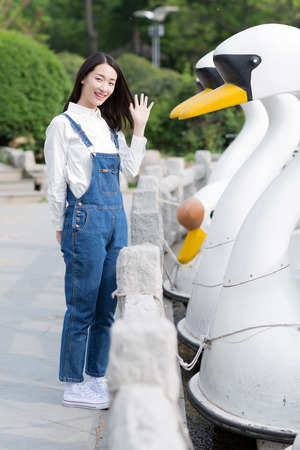 chinese adult: girl standing beside of  boats that docked beside the cement ground